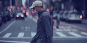 Man walking across a city street wearing a mask