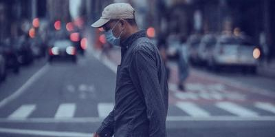 Man walking across a city street wearing a mask