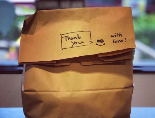 A takeout bag with a handwritten note that reads