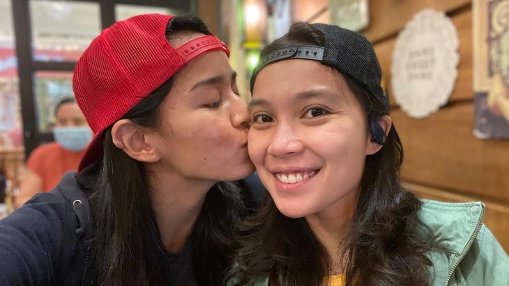 A woman kiss a woman on the cheek.