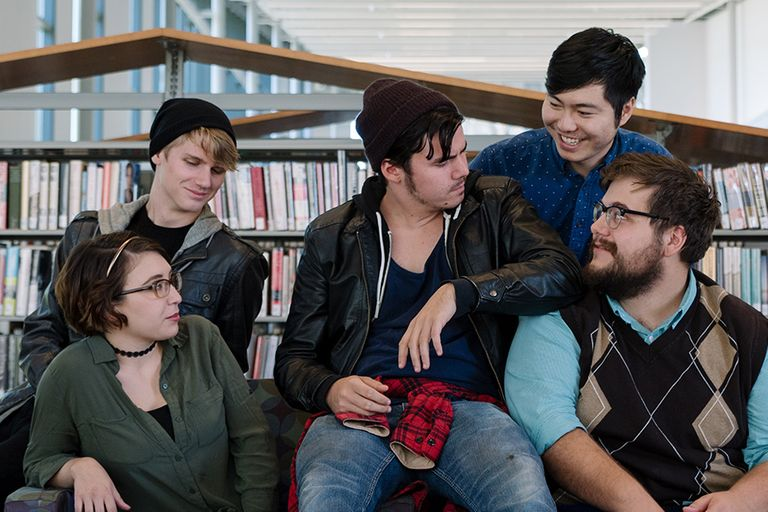 The cast of The Tutors sit on a table in a Library