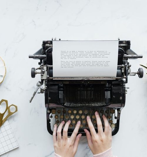 Image of a tabletop with a cup of tea and assorted items, female hands are seen typing on a typewriter