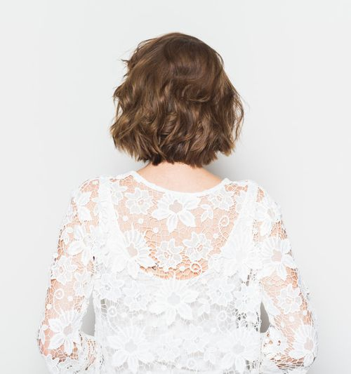 Image of a woman as seen from behind, wearing a white dress with lace flowers