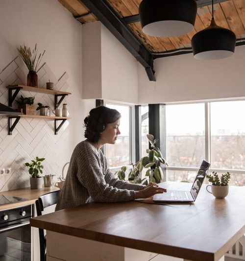 Image of a woman seated at a kitchen island, working on a laptop