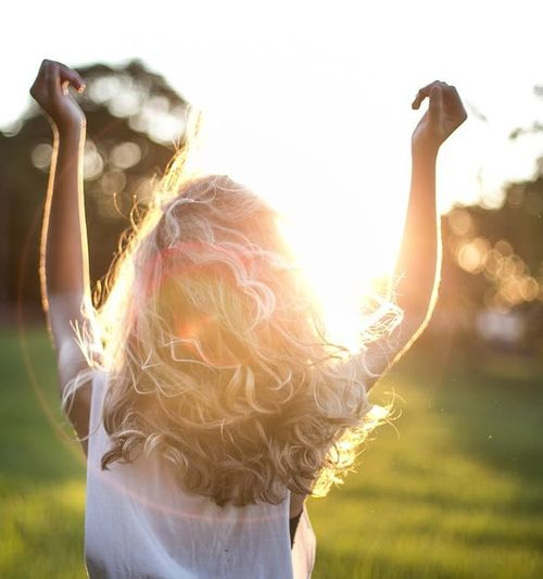 Image of a woman standing in the sunlight with back to camera and arms raised