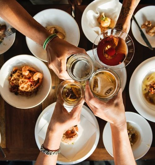 Image of four hands clicking their beers together, as seen from above over a table full of food