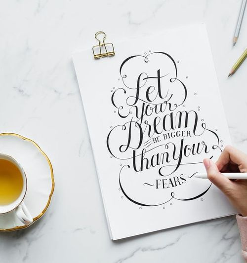 """Image of a tabletop with a cup of tea and assorted items; a female hand is seen lettering a sign that reads """"Let Your Dream Be Bigger Than Your Fears"""""""