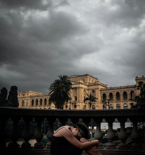 Woman sitting with head on knees in foreground, with dark and cloudy sky in background