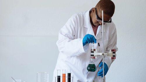 Scientist dressed in lab coat, adjusting a beaker full of fluid