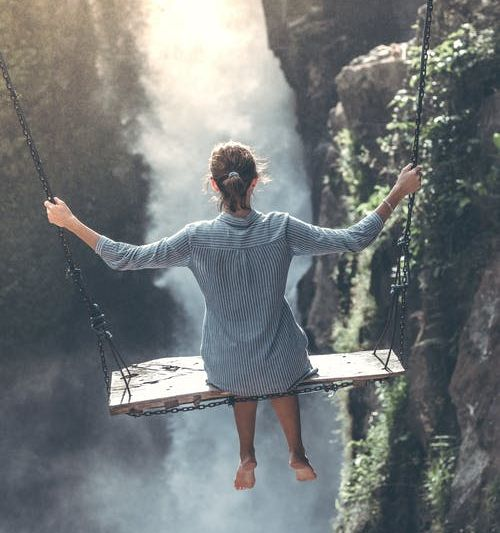 Image of a woman sitting on an oversized swing over a chasm, with back to camera