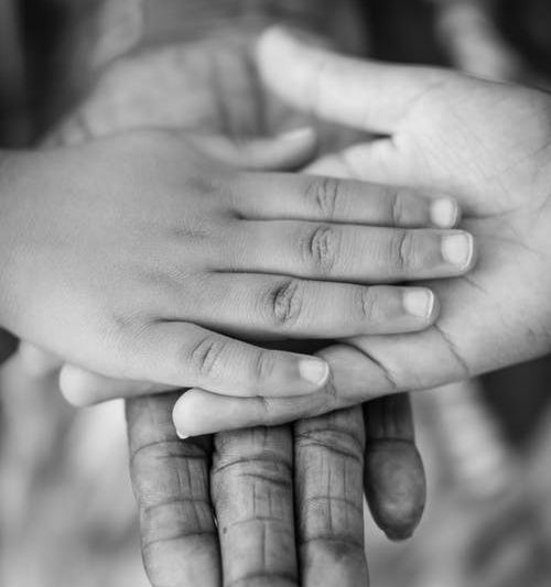 Black and white image of three individuals' outstretched hands, placed on top of each other