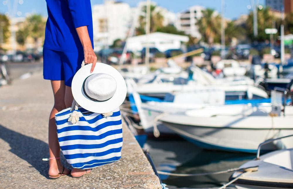donna con borsa da spiaggia al porto