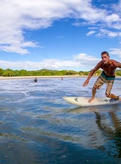 uomo che fa surf nella laguna de apoyo