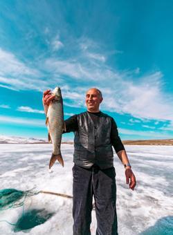 uomo pesca pesce in un lago ghiacciato