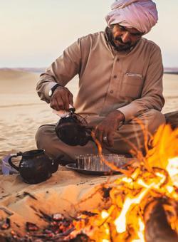 uomo accende falo nel deserto del sahara