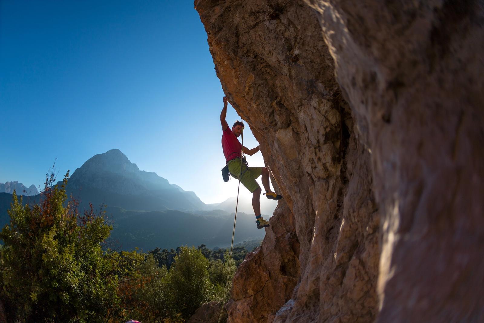 uomo si arrampica su roccia in toscana