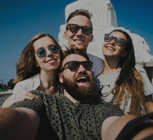 gruppo di ragazzi si scatta selfie in viaggio davanti a un monumento