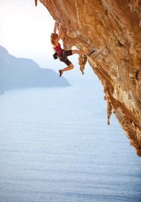 donna pratica arrampicata sportiva su roccia con vista mare