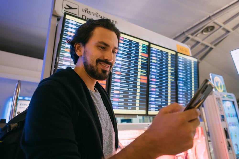 ragazzo in aeroporto guarda tabellone voli