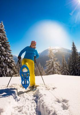 donna che cammina con le ciaspole sulla neve