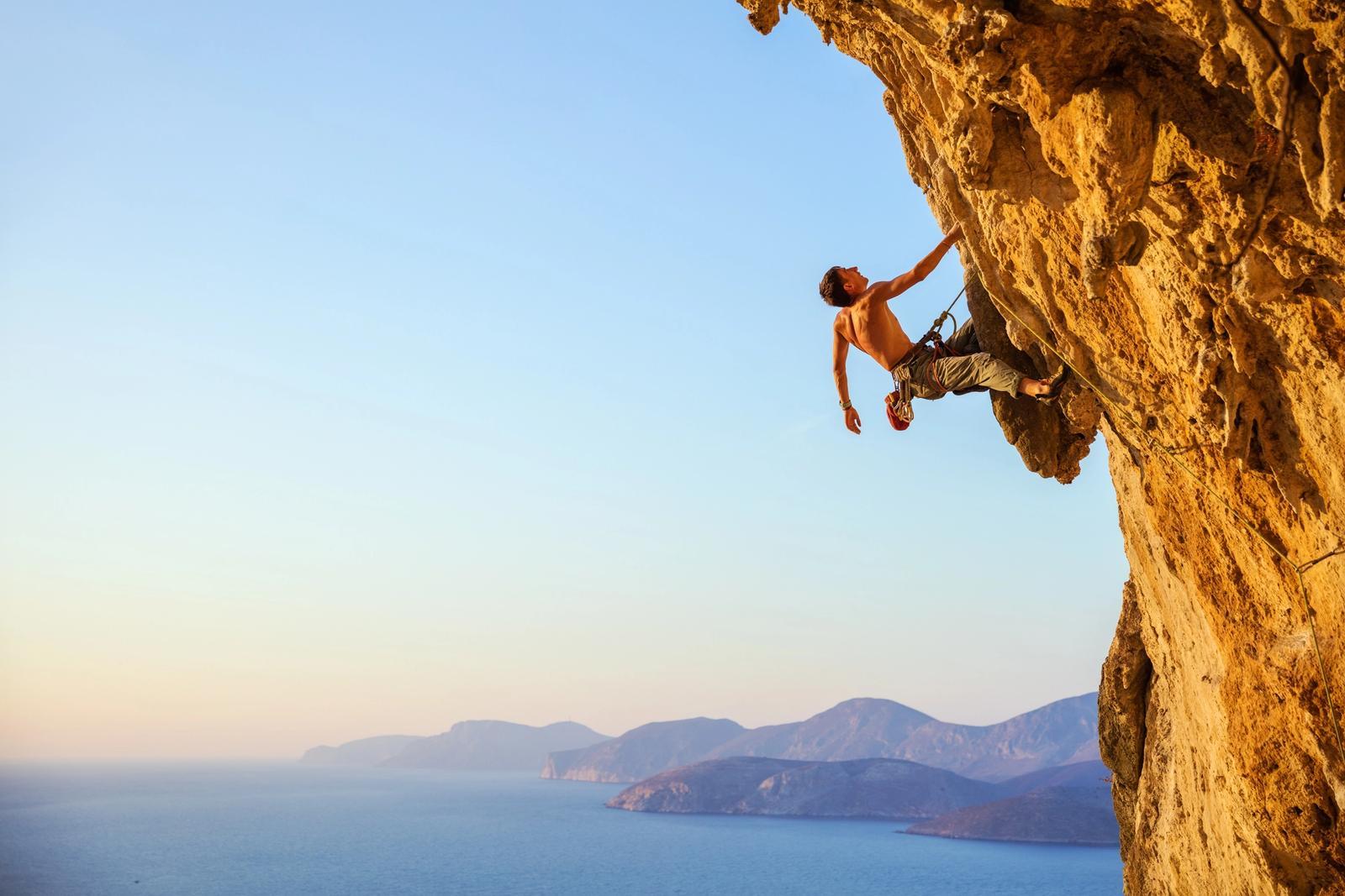 uomo si arrampica su roccia in sardegna