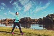 Donna che pratica nordic walking nei pressi di un lago