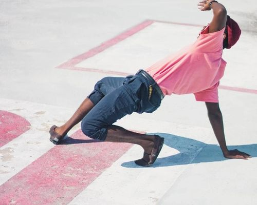 man in pink t-shirt and jeans breakdancing on a sunny day