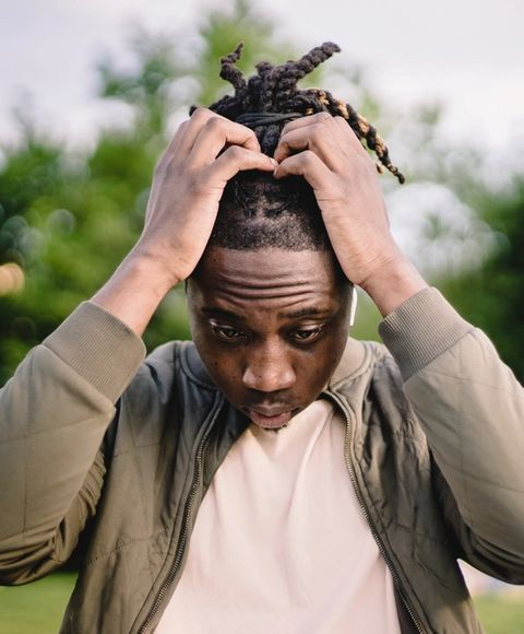 A man standing outside looking stressed with his hands in his hair