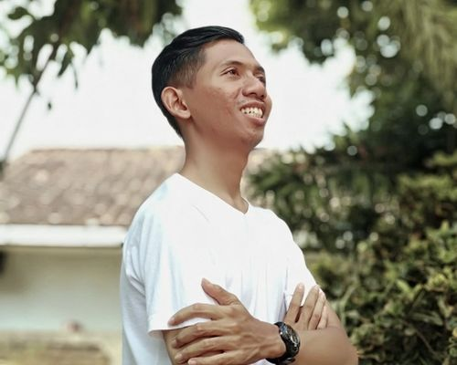 man in white t-shirt with arms folded looking off into the distance with a smile on his face