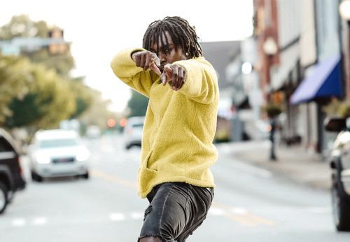 man in yellow jumper pointing at the camera