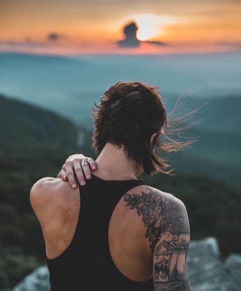 A women rubbing a sweat rash on her back