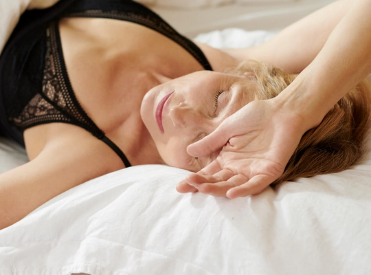 woman laying in bed, menopause sweat