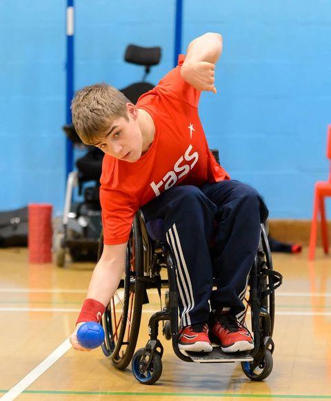 A man in a wheelchair, bowling a blue ball