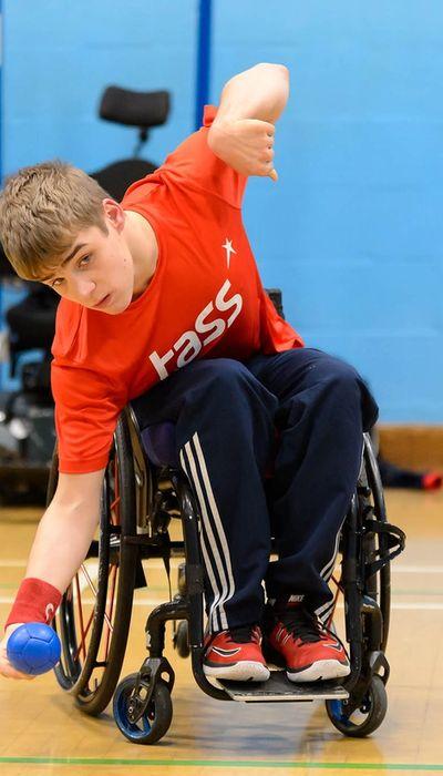 Male in a wheelchair bowling a blue ball