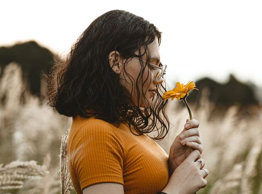 A girl in a yellow top standing in a field smelling a yellow flower