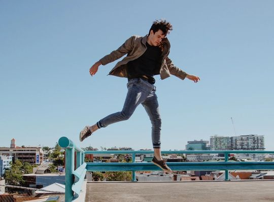 man mid-jump off a railing on top of a building on a cloudless day