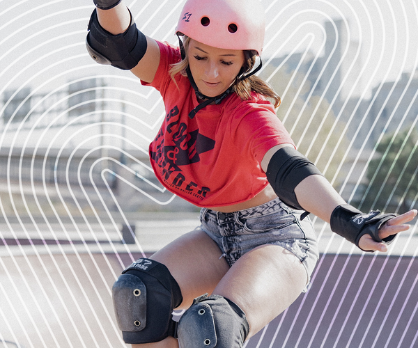 woman in pink helmet, crop top and shorts, skateboarding