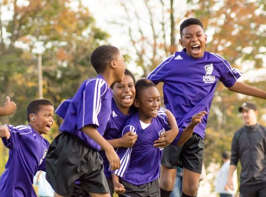 kids celebrating after scoring a goal in football
