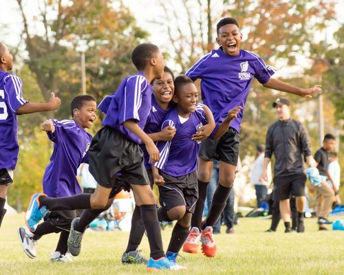 Four young kids in purple football kits celebrating a goal