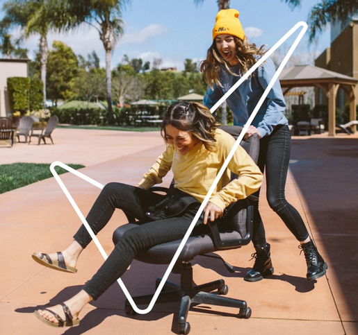 woman in a yellow hat pushing her friend outside on a computer chair. Both girls are laughing and having fun
