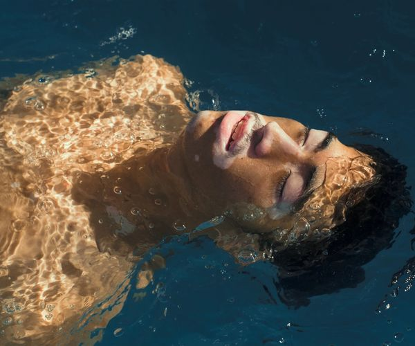 A man lays on his back in a pool with the sun shining on this face