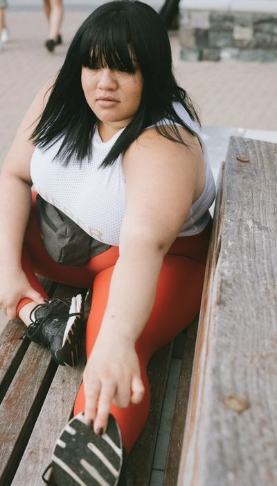 Woman with a white top and orange leggings stretching on a bench