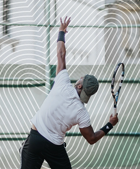 A man with a sweaty back in the middle of a tennis serve
