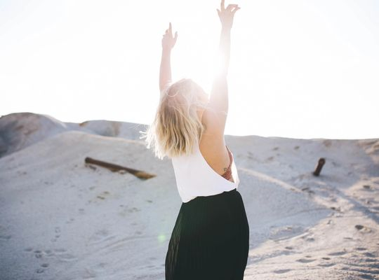 blonde woman on the beach stretching towards the sun