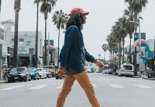 long haired man in red baseball cap walking casually across the road