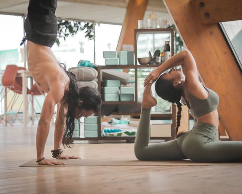 2 people doing yoga, one doing handstand the other other stretching