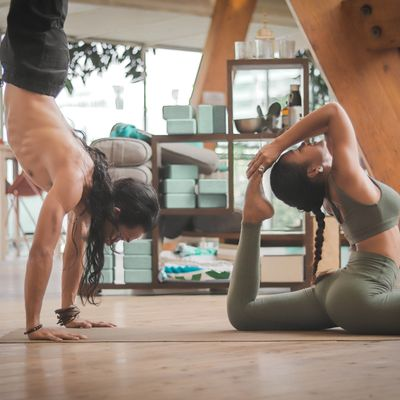 a man and woman doing yoga poses in a yoga studio