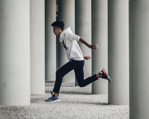 Man in white hoodie and jeans jumping between concrete pillars