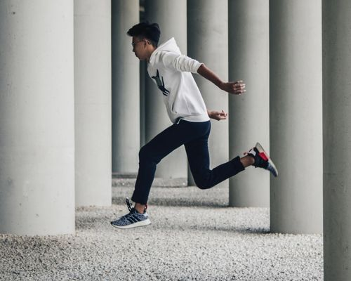 man leaping through pillars