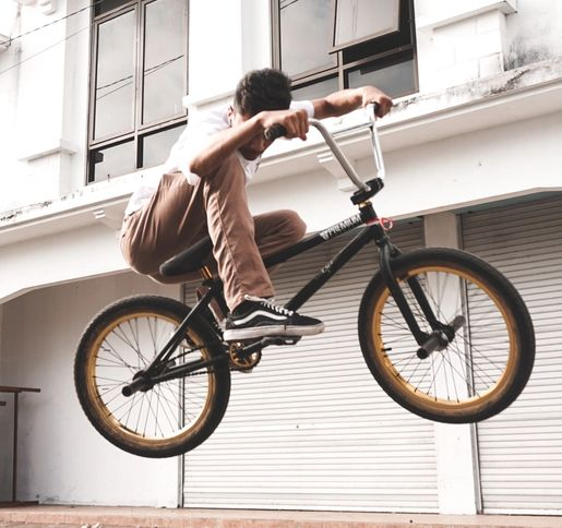 man in white t-shirt and brown trousers mid jump on a bmx